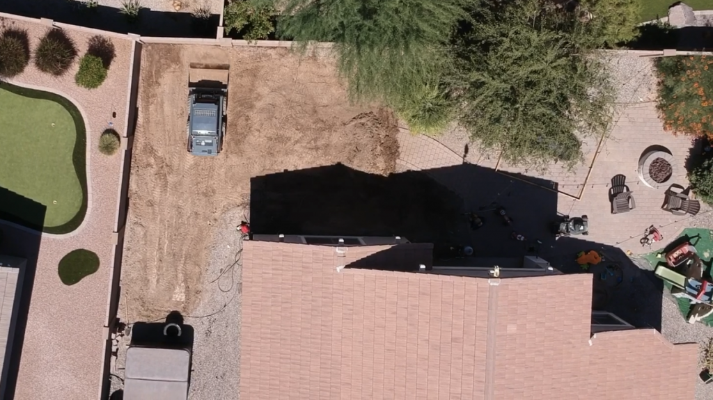 Drone view looking down at bobcat leveling out the yard