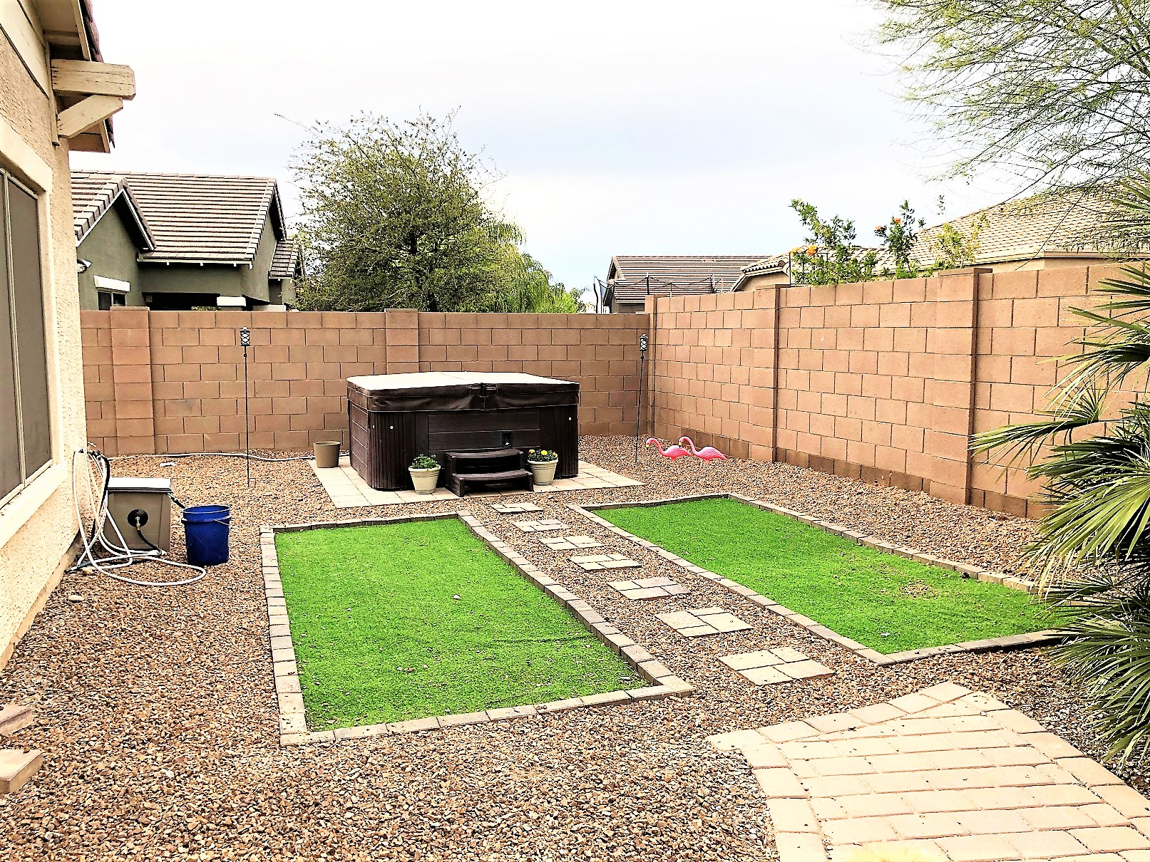 Finished yard with artificial turf and hot tub.